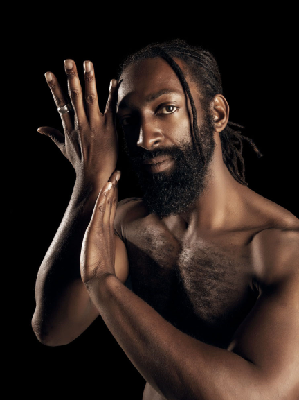 Purple Fire Crow, also known as Antoine Hunter, is bare chested, his hands gesturing toward his face. He is an award-winning African, Indigenous, Deaf, Disabled, Two Spirit producer, choreographer, film/theater actor, dancer, speaker, mentor, and Deaf advocate. He is founder of Bay Area International Deaf Dance Festival, Urban Jazz Dance Company, and #DeafWoke talk show.