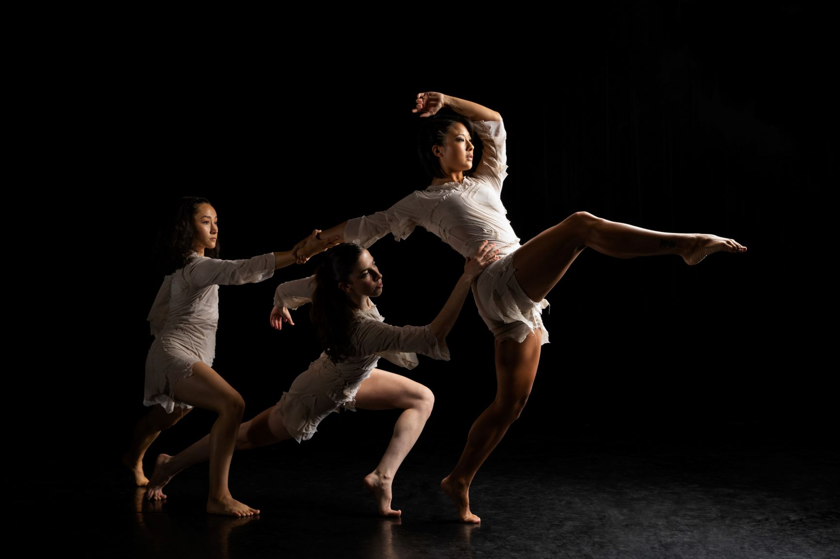 Three female dancers in white form a diagonal each with one knee bent