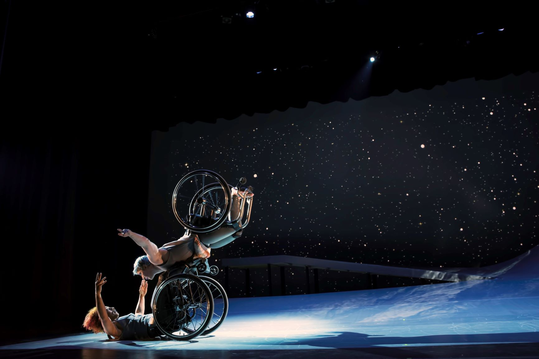 Laurel Lawson, a white woman, balances on the footplate of Alice Sheppard's wheelchair, with arms spread wide, wheels spinning. Alice, a light-skinned Black woman, opens her arms wide to receive her in an embrace. They make eye contact and smile. A starry sky fills the background, and moonlight glints off their rims. Photo: BRITT / Jay Newman