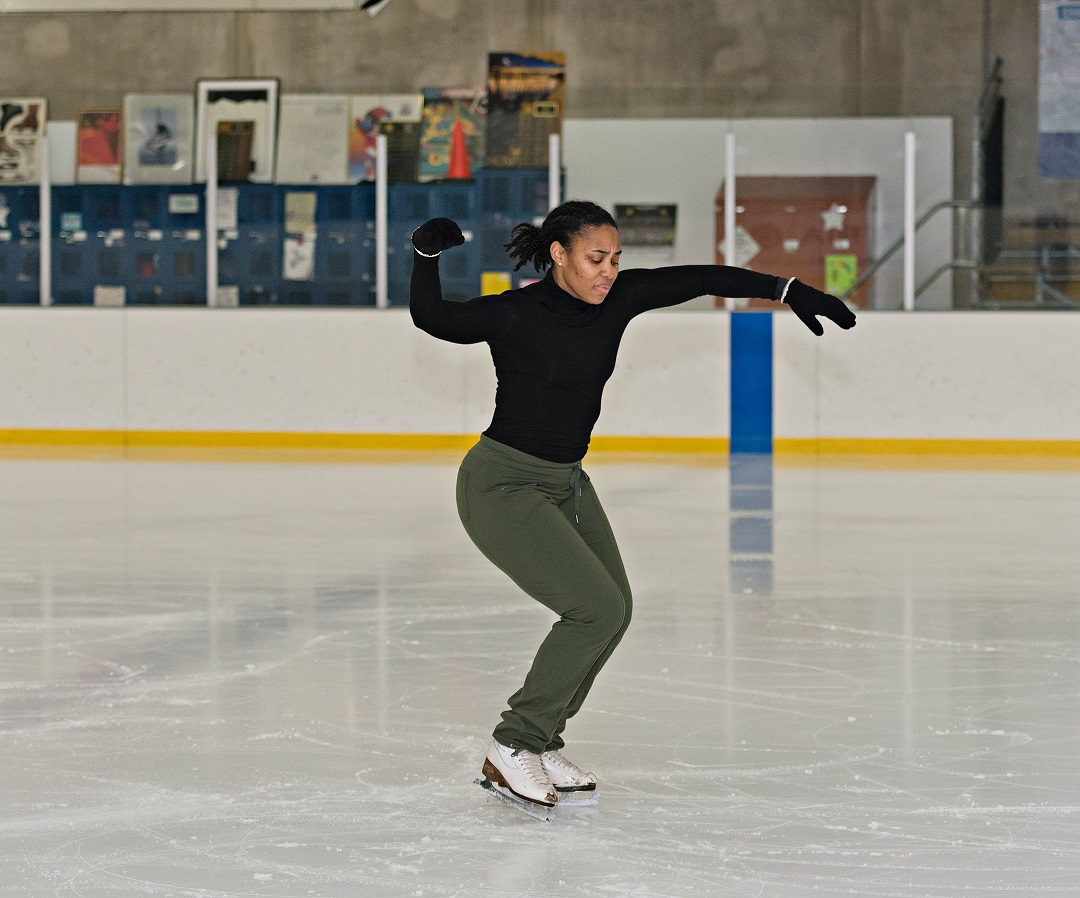 Richburg ice skates in rink wearing black top and gloves, green pants, and white ice skates