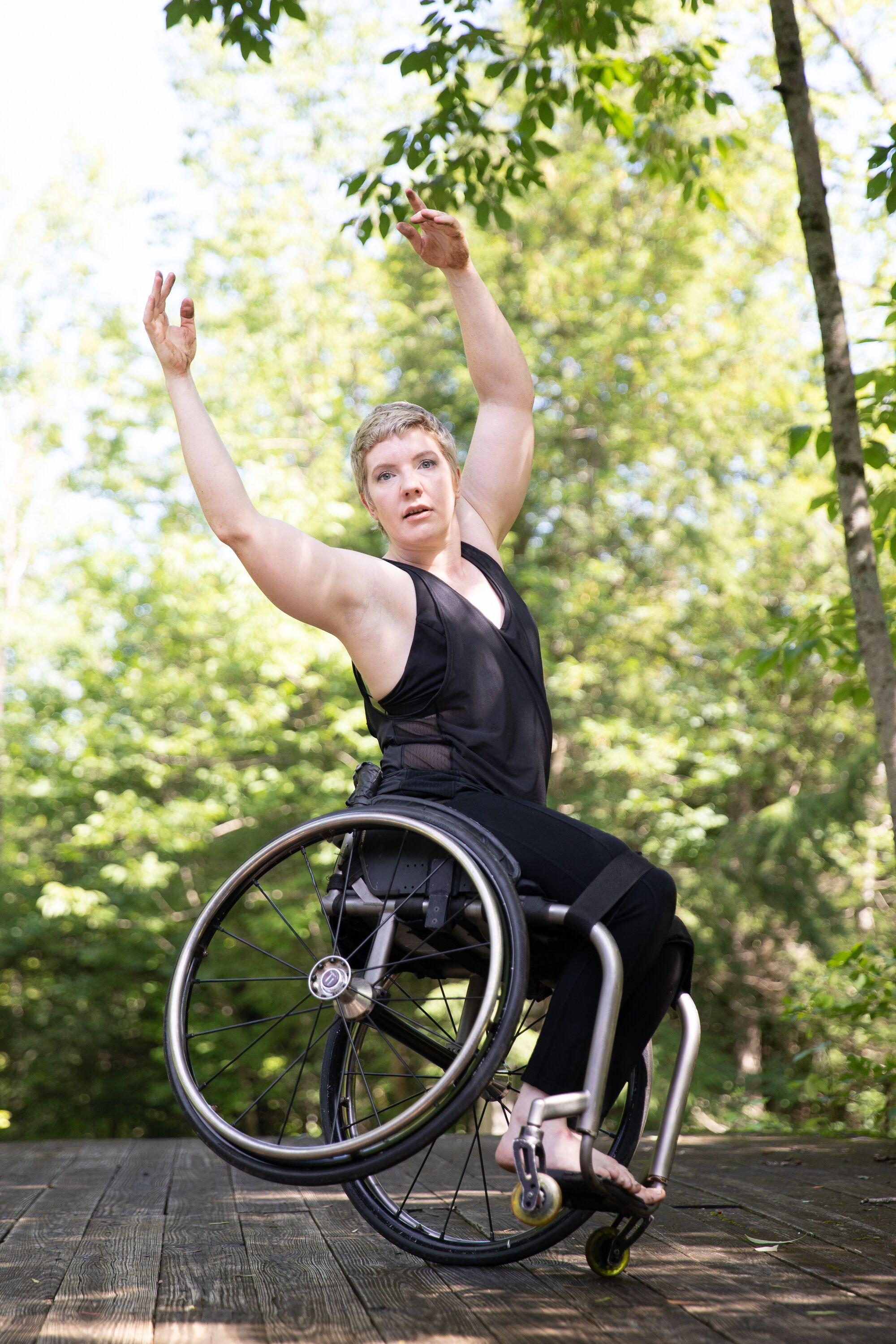 Lawson balances on one wheel, tilting away from the camera. She throws her arms overhead and looks at the viewer. Lush greenery is in the background. Lawson found that dance combined her lifelong loves of art and athleticism.