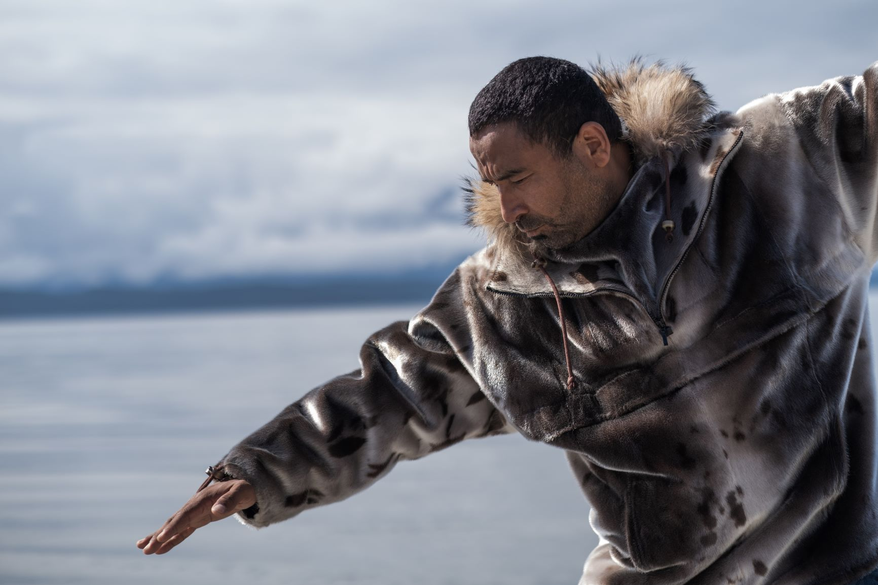 Man wearing seal-skin coat points arm with palm downward with body of water in background