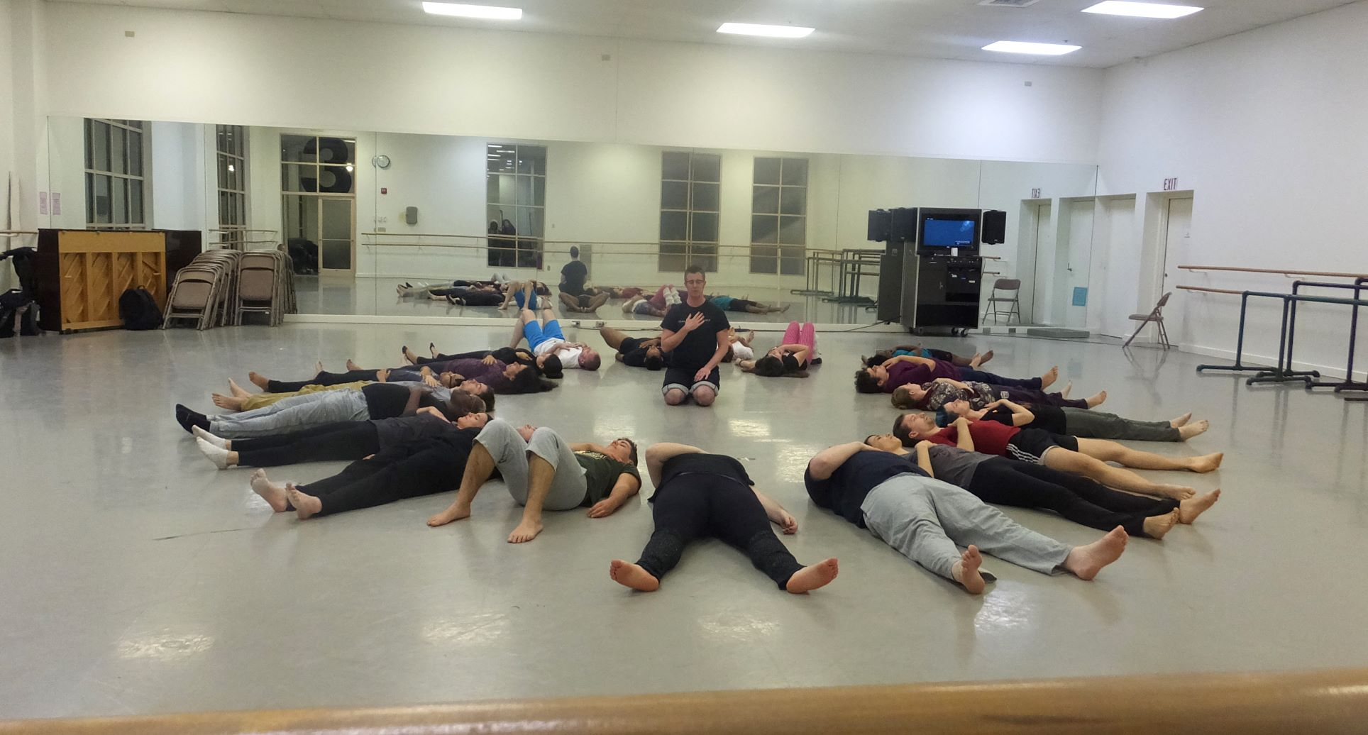 Group of people laying on their backs on the floor in a circle, heads in the middle. Dorsey sits on his knees in the center, his hand over his heart, as he speaks to the group