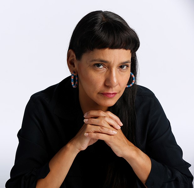 Simas, wearing a black shirt and patterned hooped earrings, poses with her hands clasped below her her chin