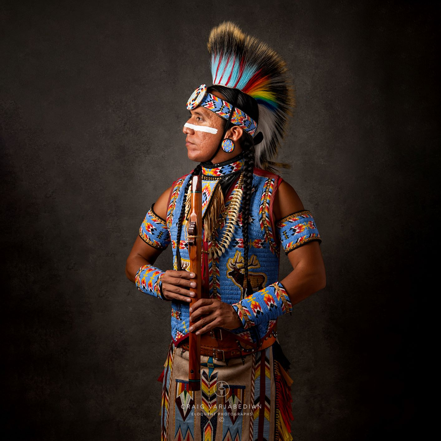 Man in traditional Native garb including beaded and feather headress stands in profile holding wooden flute