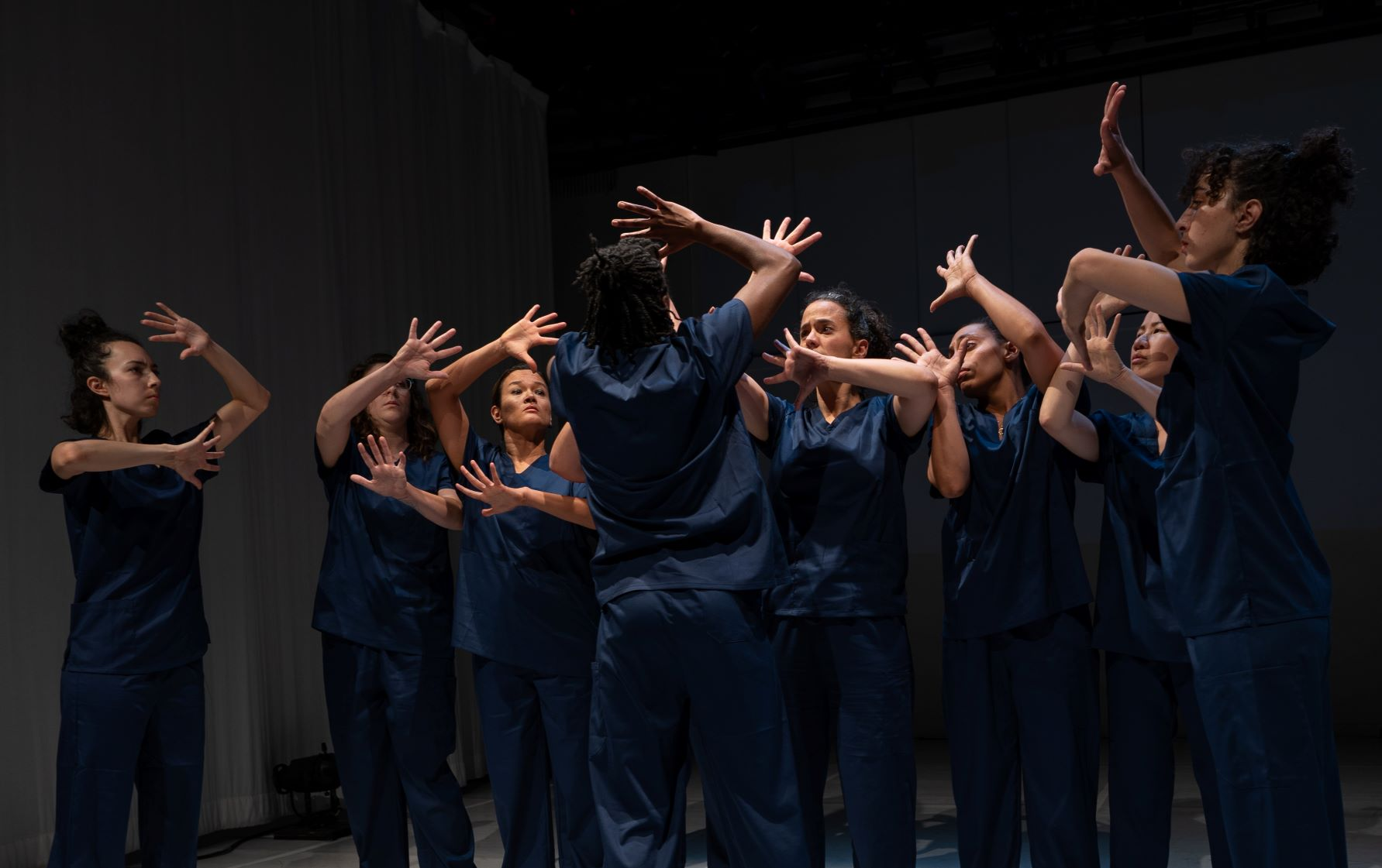 Hunter's Deaf's IMPRISONED explores what it means to be in a prison within a prison as a Deaf person moving through the criminal justice system. A group of performers in dark blue garments stretch their hands in front of their faces. The 2018 Urban Jazz Dance Company work navigates the tension between what Hunter called Deaf utopia and Deaf diaspora.