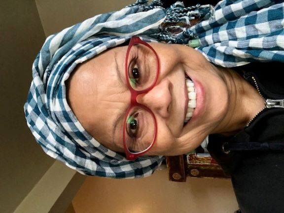 Woman with red glasses and a blue and white head scarf smiles