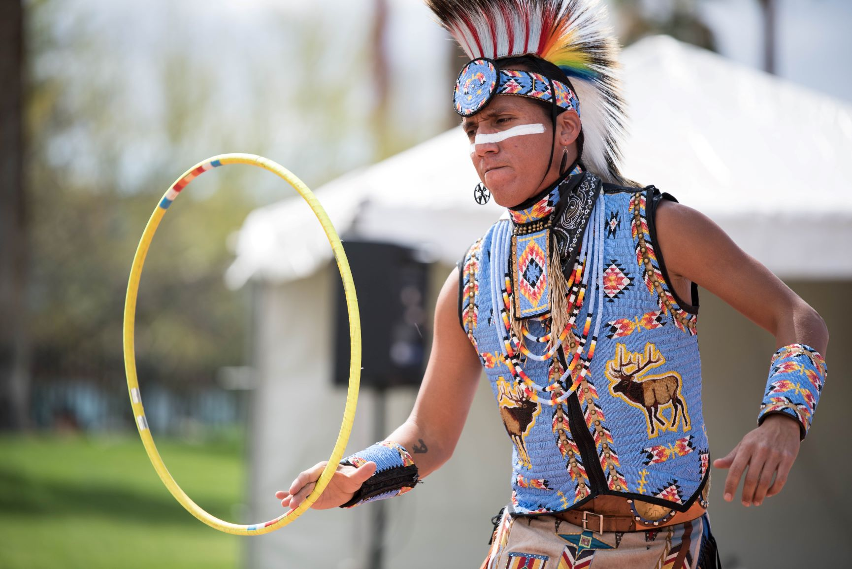 Man in traditional Native headress and light blue vest dances outdoors while holding yellow hoop